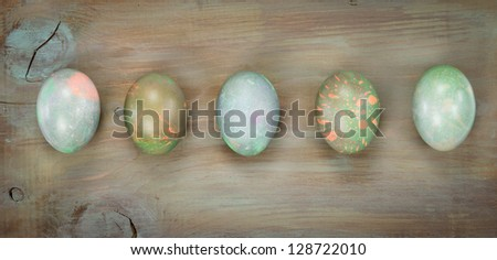 Five marbled Easter eggs on a board surface - stock photo