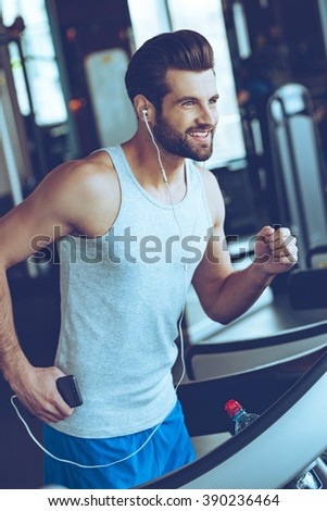 Five miles with pleasure. Cheerful young handsome man in headphones looking away with smile while running on treadmill at gym - stock photo
