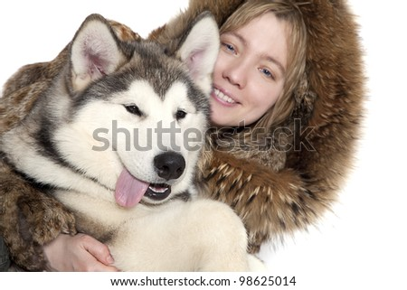 Five month old malamute puppy with a girl. Focus on a dog - stock photo