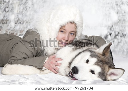 Five month old malamute puppy with young caucasian woman - stock photo