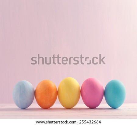 Five multicolored Easter eggs on wooden painted background - stock photo