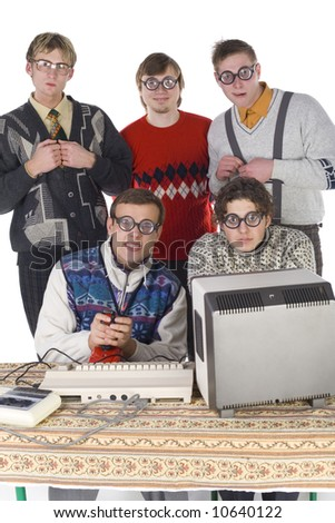 Five nerdy guys looking at camera. Two of them are sitting in front of old-fashioned computer. Others are standing behind them. They are looking very funny. Front view, white background - stock photo