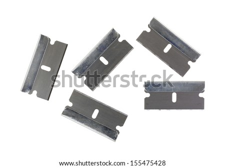 Five new razor blades arranged on a white background. - stock photo