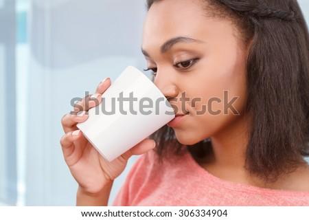 Five oclock tea. Portrait of young attractive mulatto girl drinking some tasty tea. - stock photo