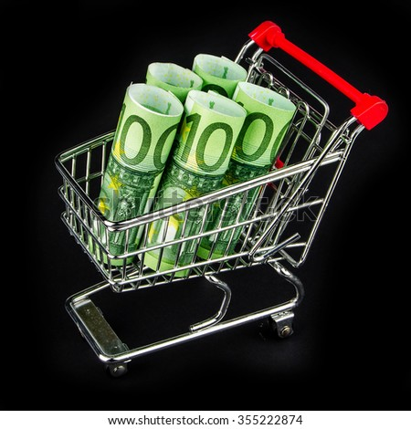 five one hundred euro banknote rolls laying in shopping cart on black background - stock photo