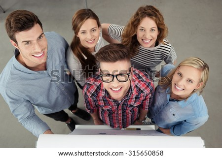 Five Optimistic Office Workers Smiling at the Camera From the Top View Inside the Office. - stock photo