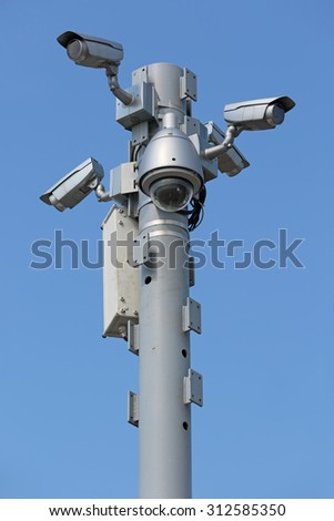 Five outdoors cameras surveillance and control on the background of blue sky - stock photo