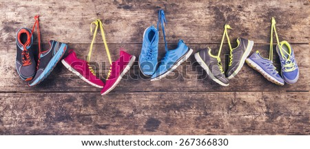 Five pairs of various running shoes hang on a nail on a wooden fence background - stock photo