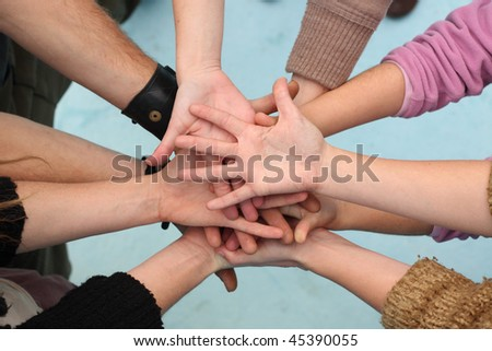 Five people join their hands together