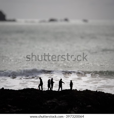 Five people on an adventure at the coast with the ocean behind them. A family of five in silhouette on a coastal expedition at dawn. Five friends on a clifftop overlooking the ocean. - stock photo