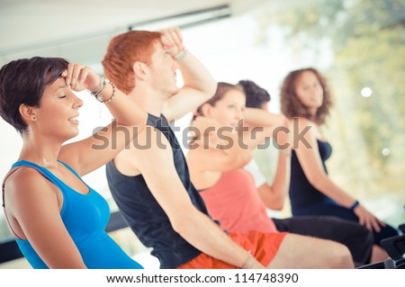 Five people tired in the gym, exercising their legs doing cardio training ,Italy