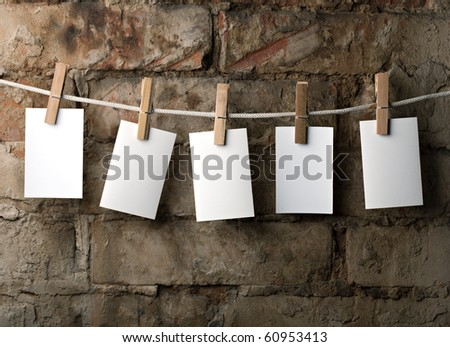 five photo paper attach to rope with clothes pins on brick background - stock photo
