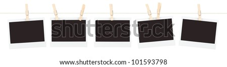 Five pieces of blank instant film held on a string with clothespins isolated on white. - stock photo