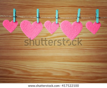 five pink hearts hanging on a cord on a wooden background, love background, place for text - stock photo