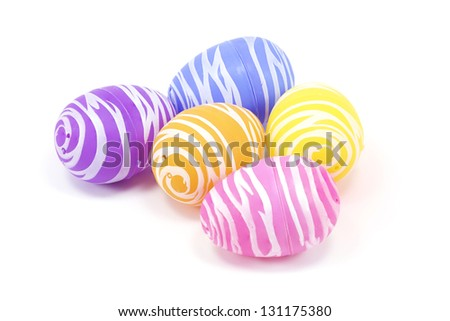 Five plastic painted easter eggs on white with room for copy