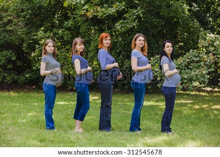 Five pregnant women in the same clothes outdoor. Group of pregnant women touching their bellies