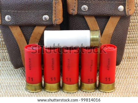 five red and white shotgun cartridges 11 and 12 and hunting bag