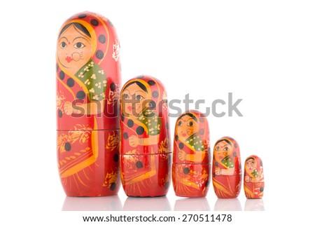 Five red Babushka on white reflective background. - stock photo
