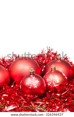 five red Christmas balls and tinsel isolated on white background