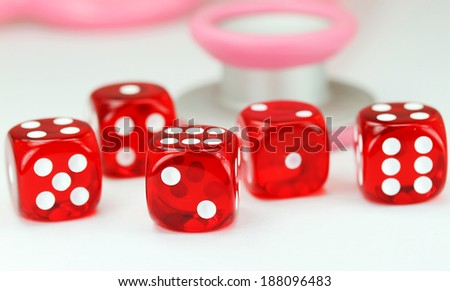 Five red translucent dice with white numbers in front of a pink stethoscope, asking the question do you gamble with your health?