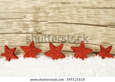 Five red twinkling stars in the snow with wooden background - stock photo