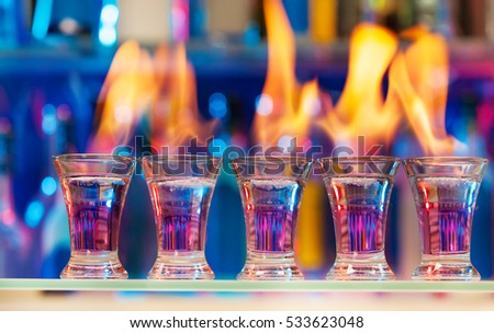Five shot glasses with flaming cocktails