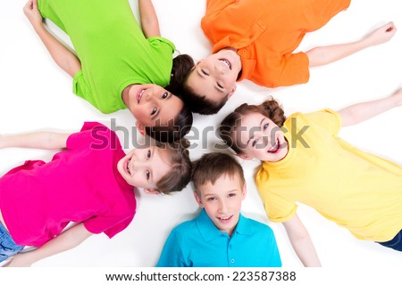 Five smiling children lying on the floor in a circle in bright t-shirts. Top view. Isolated on white. - stock photo
