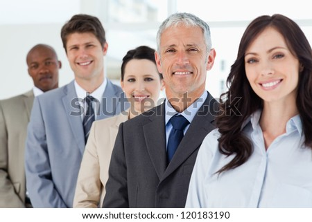 Five smiling employees standing around their manager - stock photo