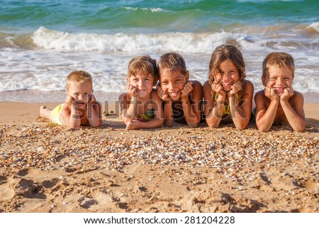 Five smiling kids enjoying on the sand on beach - stock photo