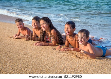 Five smiling kids lying down on the beach in sand near water