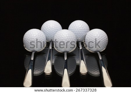 Five spoons and golf balls on a black glass desk