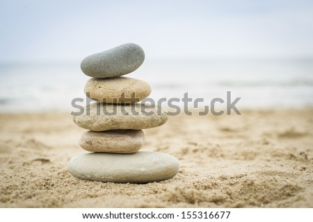 Five stones balanced on top of eachother on a sandy beach