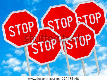 Five stop sign against blue sky background - stock photo