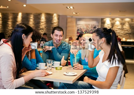 Five student friends communicating in cafe - stock photo
