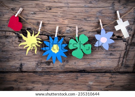 Five Symbols Or Icons Like Two Hearts, A Sun, A Flower And One Four Leaf Clover Hanging With Clothespins Or Pegs On A Line On Wooden Background, Vintage, Retro And Old Fashion Style With Frame - stock photo