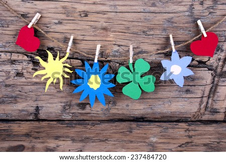 Five Symbols Or Icons Like Two Hearts, A Sun, A Flower And One Four Leaf Clover Hanging With Clothespins Or Pegs On A Line On Wooden Background, Vintage, Retro And Old Fashion Style - stock photo