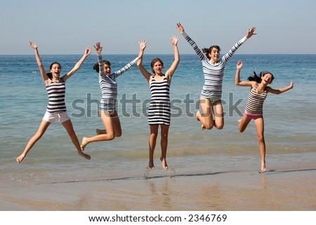 Five teenage girls jumping on the beach - stock photo