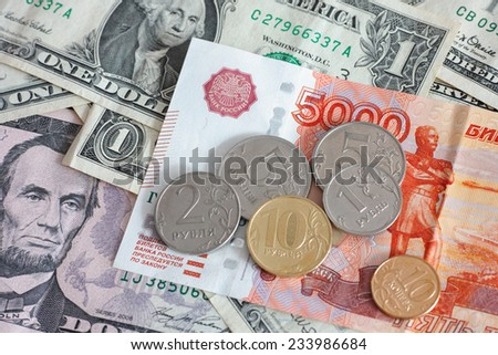 Five thousand rubles with ruble coins on dollar banknotes. - stock photo
