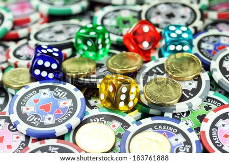 Five translucent colored dice laying on a pile of gambling chips of various denominations, with some gold coins also lying on the gambling chips  - stock photo
