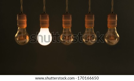 Five Vintage Hanging Incandescent Light Bulbs with One Illuminated - stock photo