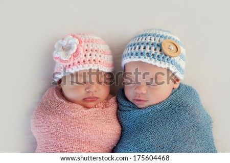 Five week old sleeping boy and girl fraternal twin newborn babies. They are wearing crocheted pink and blue striped hats. - stock photo