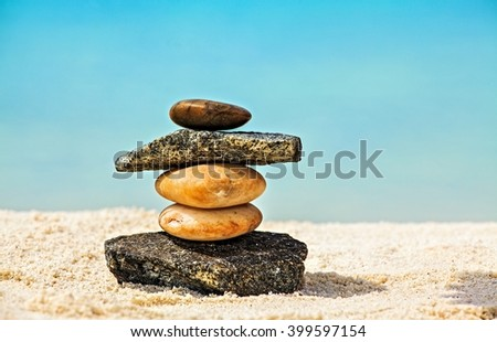 Five white and brown stones are on sandy beach - stock photo