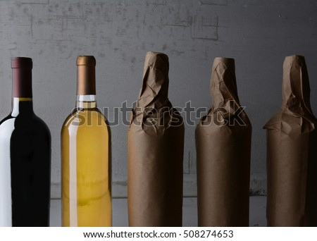 Five Wine Bottles, three wrapped in plain paper with one red wine and one white. Strong side light with copy space.
