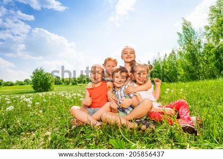 Five wonderful children smile and sit together on a beautiful meadow