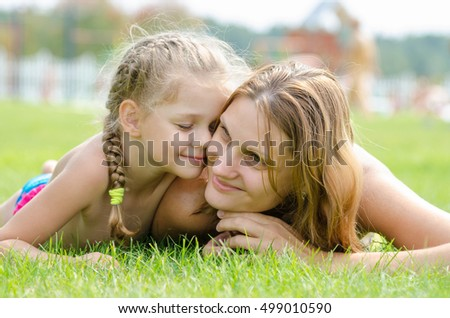 Five-year cute daughter pressed her face to the mother's face on a green grass lawn