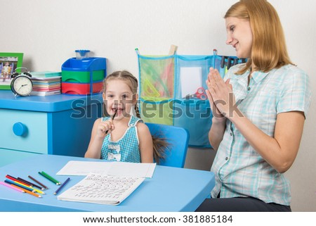 Five-year girl and a tutor is fun sitting at the table and enjoy - stock photo