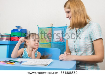 Five-year girl funny looks at the tutor who helps her to write letters correctly - stock photo