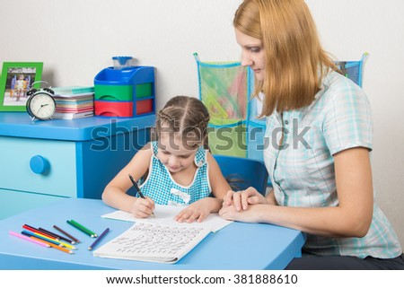 Five-year girl learns to write letters correctly, a tutor helps her - stock photo