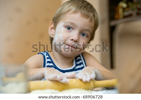 Five year old boy helps his mother make cakes - stock photo