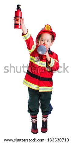 Five year old boy in a suit with a fire extinguisher firefighter stands in one hand and a megaphone in the other